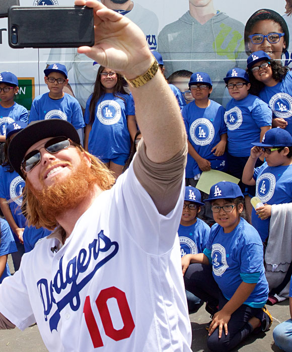 Justin Turner helps distribute glasses to kids at Betty Plasencia Elementary School in Los Angeles.