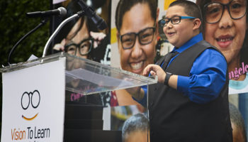 Santiago, a fifth grader in Los Angeles, tells the crowd how glasses have helped him