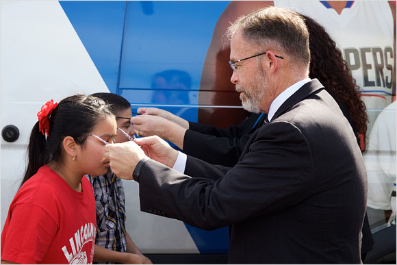 Chris Steinhauser, Superintendent of the Long Beach Unified School District, helps children with their new glasses at George Washington Middle School in Long Beach.
