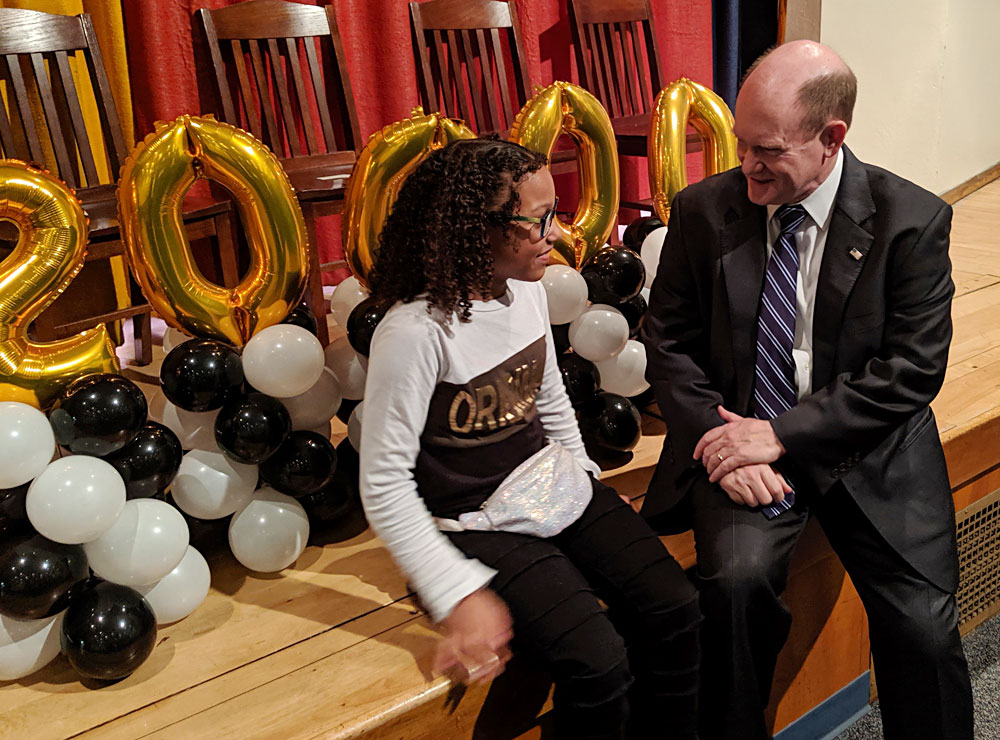 Senator Chris Coons chats with the 200,000th child to receive glasses from Vision To Learn