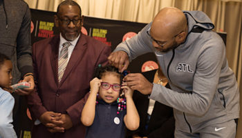 Vince Carter of the Atlanta Hawks helps a student with her new glasses while Dr. Stephen Green, Superintendent of DeKalb County Schools, looks on. Toney Elementary, December 10, 2018, Atlanta, GA.