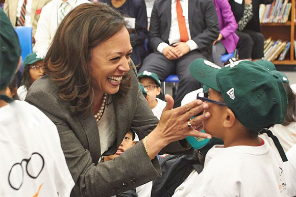 Former Attorney General, now Vice President-Elect Kamala Harris helps a student from Franklin Elementary School try on new glasses at Vision To Learn's launch in Oakland, May 2014.