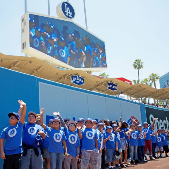L.A.-area students wave from the outfield as the Dodgers host them at Dodgers Stadium for some summer fun