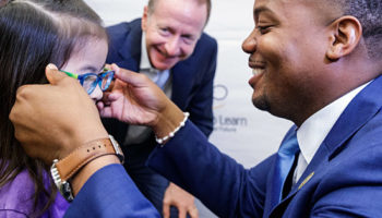 "Orleans Parish School Board Member Ethan Ashley puts glasses on a Foundation Preparatory Charter School ""Prepster"" as Austin Beutner looks on, April 26, 2018"