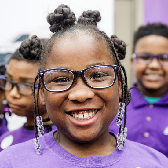 Student at Foundation Preparatory Charter School in New Orleans showing off her new glasses.