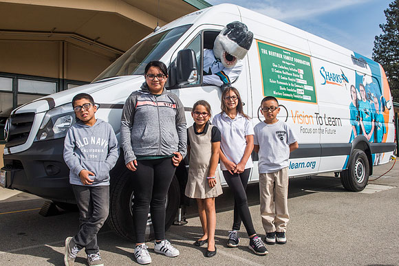 San Jose Sharks mascot S.J. Sharkie with some children who received glasses at Hubbard Media Arts Academy in San Jose, October 2017.
