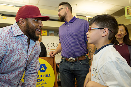 Ray Lewis admiring student's new glasses