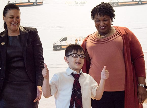 Thumbs up, indeed! Atlanta Public Schools Superintendent Dr. Meria Carstarphen and Former Georgia House Minority Leader Stacey Abrams flank a Barack and Michelle Obama Academy student who just received his new glasses.