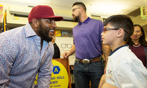 Ray Lewis hands out glasses to children at Vision To Learn event
