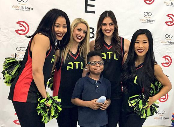 Atlanta Hawks Cheerleaders celebrate with a student.