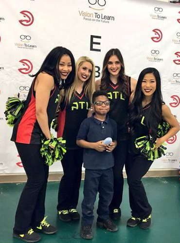 Atlanta Hawks cheerleaders celebrate a student's new glasses, at Parkside Elementary School in Atlanta