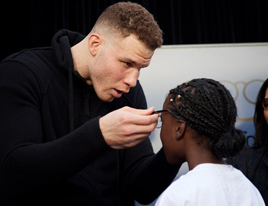 Blake Griffin helping student with new glasses