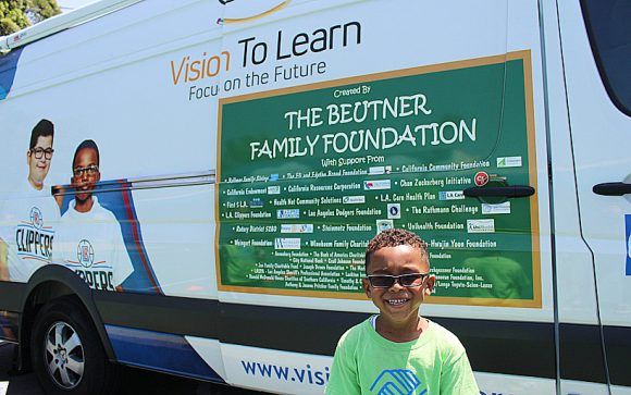 Boy showing off new glasses in front of mobile clinic