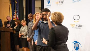 Franklin Walker, Chief Schools Administrator of Jersey City Public Schools, and Laura Overdeck, Chair of the Overdeck Family Foundation, look on while a Frank R. Conwell student receives his glasses.