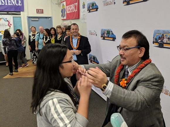 Rep. John Mizuno helps a Dole Middle Schooler with her new glasses as Lt. Governor Josh Green and others look on.