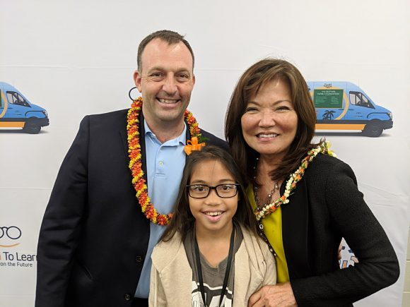 Lt. Governor Josh Green and Sharon Brown, President of Hawaiian Bank Foundation, flank a Dole Middle Schooler as she shows off her new glasses.