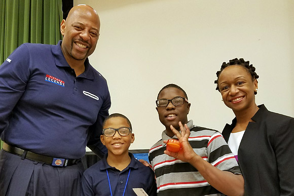 NBA legend Earl Cureton and Dr. Joneigh S. Khaldun, Executive Director of the Detroit Health Department, help kids receive their new glasses at Ronald Brown Academy in Detroit, February 2017.