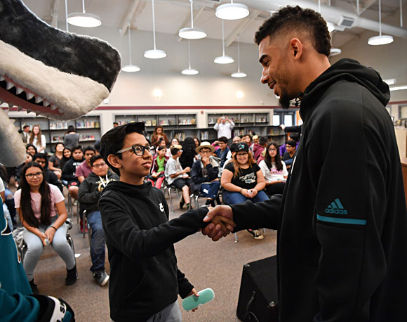 San Jose Sharks' Evander Kane help Columbia Middle Schoolers try on their new glasses.