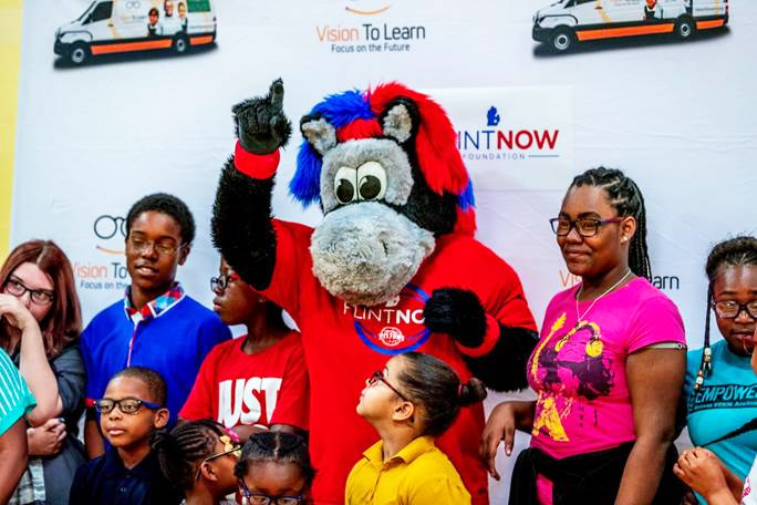 FlintNOW mascot with kids showing off their new eyeglasses