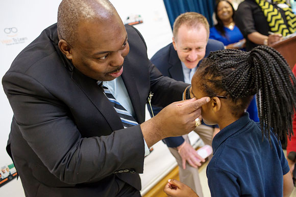 Interim Jackson Public Schools Superintendent Dr. Fredderick Murray helps a child with her new glasses, May 2017.