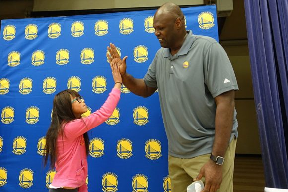 Retired NBA center Adonal Foyle high-fives a girl who just received glasses from Vision To Learn