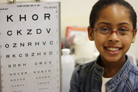 Girl in new glasses next to eye chart