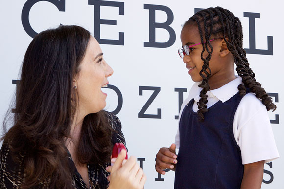 Gillian Zucker, President of Business Operations for the Los Angeles Clippers, with a girl who just received her new glasses at Warren Lane Elementary School in Inglewood.
