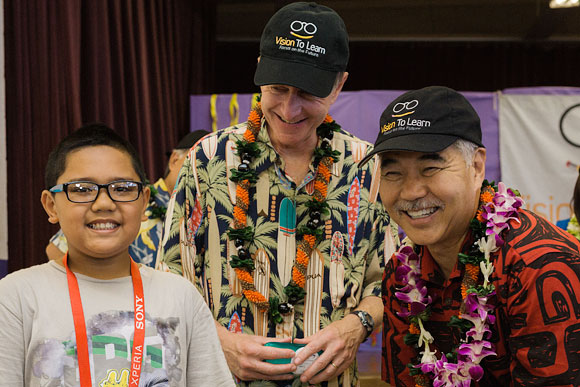 Governor David Ige helps give glasses to children at Vision To Learn's Hawaii kickoff event, at Kalihi Waena Elementary School in Honolulu, August 2015.