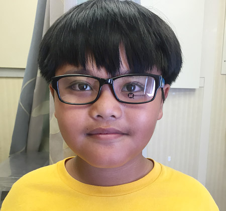 Male student in Hawaii tries on new glasses