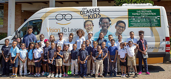 Kids with their new glasses in front on the Jackson, MI mobile clinic