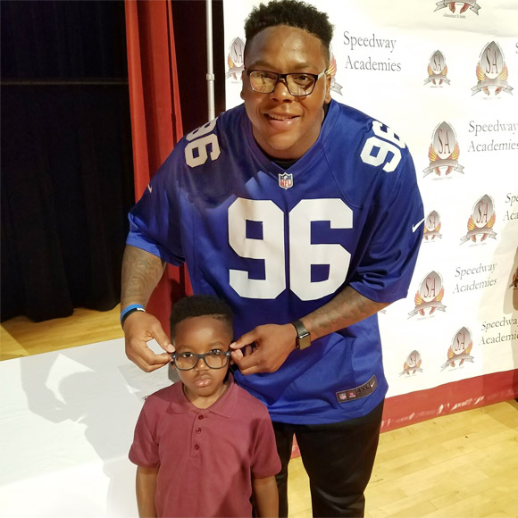 Jay Bromley helps student with new glasses