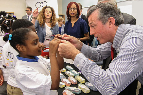 Delaware Governor John Carney helps a girl with her new glasses at a distribution event for students of Kuumba Academy and Great Oaks Charter Schools, April 2017.