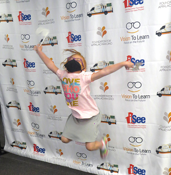 child jumps for joy with new glasses