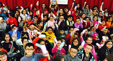 Many children holding up their new eye glasses