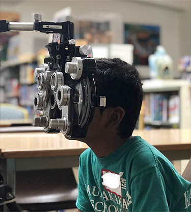 Student receiving an vision screening, courtesy of The Molokai Project