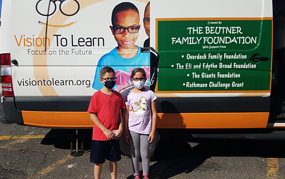A brother and sister team with their new glasses in Paterson. They were very excited to be able see their books and screens clearly again.