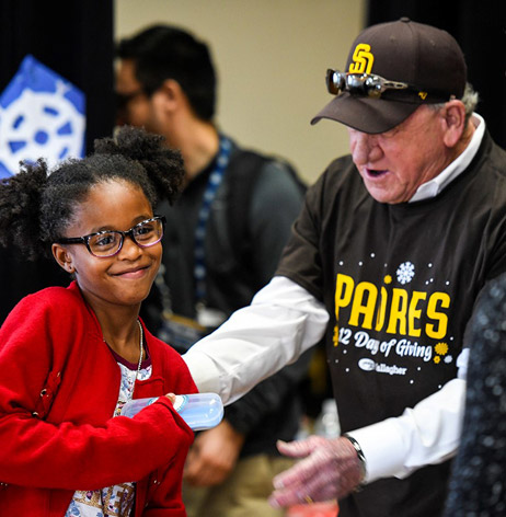 Former Padres All-Star pitcher Randy Jones helps a student receive her glasses.