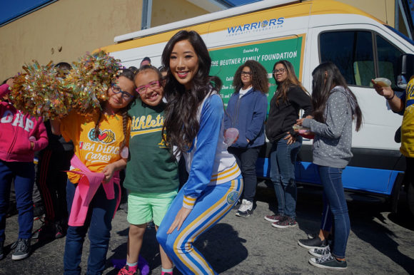 Golden State Warrior Dancer with students after receiving their new eyeglasses