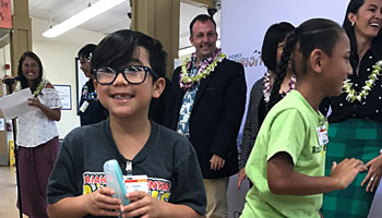 Smiling student receiving new glasses at Waimanalo Elementary