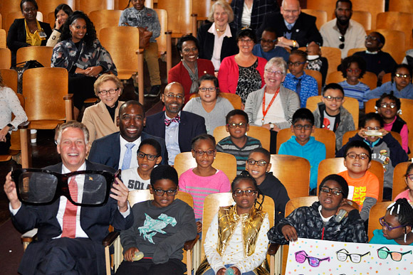 Governor Terry McAuliffe holds a large pair of glasses at the Vision To Learn kickoff event in Richmond, October 2017. Also sitting with some of the children who received glasses are Mayor Levar Stoney, Secretary of Education Dr. Dietra Trent, Interim Superintendent Thomas Kranz, Anne Holton, and other guests.