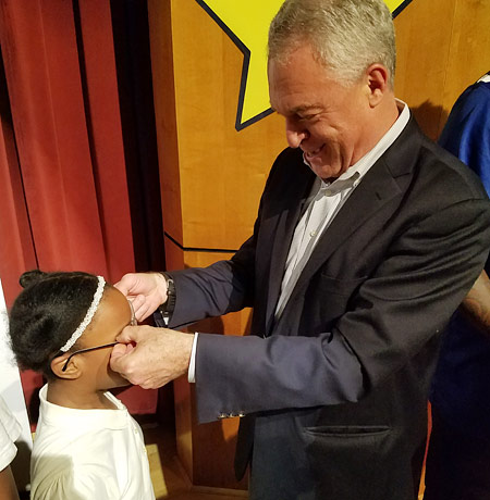 Newark Public Schools Superintendent Christopher D. Cerf helps a girl with her new glasses at Speedway Academies, May 2017.