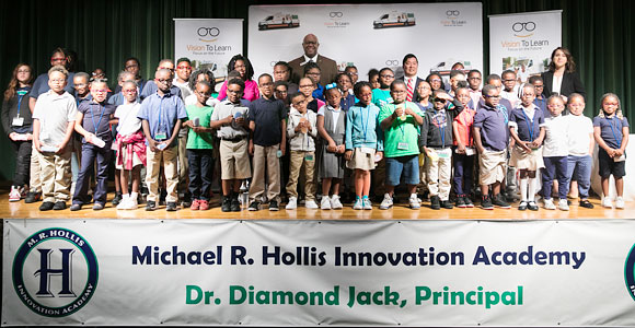 A stage full of kids who just received their glasses at Hollis Innovation Academy in Atlanta, August 2017. Atlanta Public Schools Board of Education District 2 representative Byron Amos stands tall in the back row.